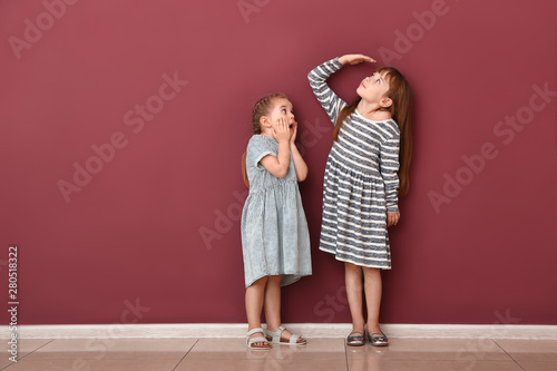 Fotomural  Little girls measuring height near wall