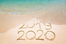 Goodbye 2019 Happy New Year 2020 Lettering On Beach With Wave And Clear Blue Sea On Sunny Day. Handwritten Inscription 2019 And 2020 On Beautiful Golden Sand Beach. New Years 2020 Replace 2019 Concept