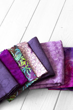 Various Fabric Material Sample Swatches,  With A Purple Theme, On A White Wood Background
