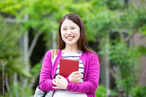 Fototapeta 本を持つ女子学生