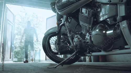 Photo biker enters the garage and goes to the chopper