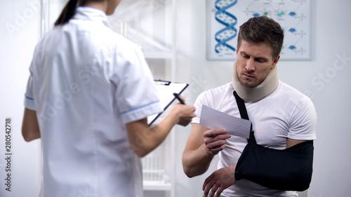 Fotografering Patient in foam cervical collar and arm sling reading doctors prescription