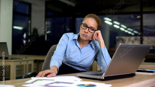 Photo Upset and tired business woman sitting at office late at night, troubles at work