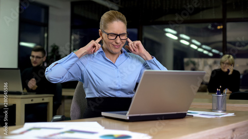Irritated lady closing ears with fingers, noisy colleagues distracting from work Fototapet