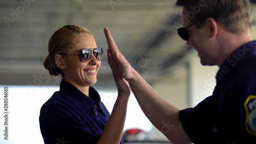 Smiling police teammates giving high-five to each other, coworking concept, team - 280546165