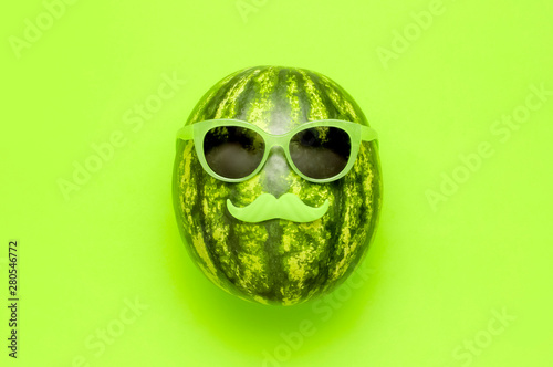 Summer funny watermelon in green glasses and with green mustache on bright green background top view flat lay. Minimal fruit concept. Creative product idea, summer festival, summer background - 280546772