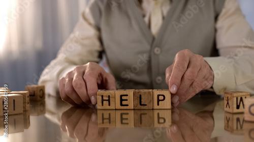 Fotomural  Senior man making word help of wooden cubes on table, parkinson disease, tremor