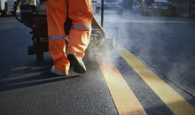 Selective Focus And Low Section Of Road Worker With Thermoplastic Spray Road Marking Machine Working To Paint Yellow Lines With Steam On Asphalt Road Surface In Evening Time, Construction Concept
