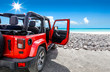 canvas print picture - A red jeep on sandy beach and beuatiful blue sunny sky view in summer time.