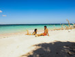 Lovely couple relaxing at the white sandy beach with palm trees in Onok Island in Balabac Palawan in Philippines