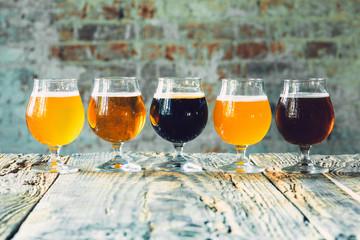 Čaše različitih vrsta tamnog i svijetlog piva na drvenom stolu u redu. Hladna ukusna pića pripremaju se za zabavu velikog prijatelja. Koncept pića, zabava, sastanak, oktoberfest.