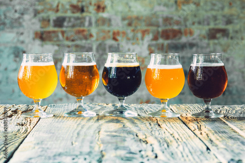 Tableau sur Toile Glasses of different kinds of dark and light beer on wooden table in line