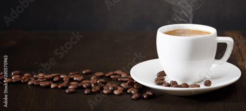 A cup of coffee and coffee beans on the table. Black background.