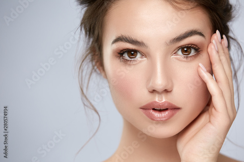 Obraz close-up portrait of beautiful girl with big eyes and perfect skin looking to camera - fototapety do salonu