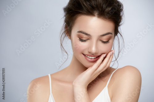 Obraz beautifuk girl with golden make-up and in white t-shirt touching cheek and smiling - fototapety do salonu