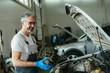 worker repairing car engine in car service