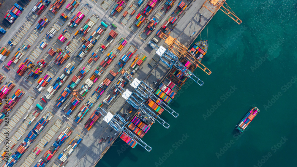 Fototapeta Aerial view cargo ship terminal, Unloading crane of cargo ship terminal, Aerial view industrial port with containers and container ship.