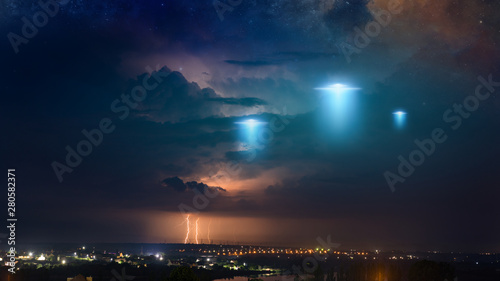Tuinposter UFO Extraterrestrial aliens spaceship fly above small town, ufo with blue spotlights in dark stormy sky.