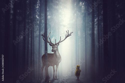 Foto auf Gartenposter Hirsch Kleines KInd steht vor einem großen Hirsch im Wald