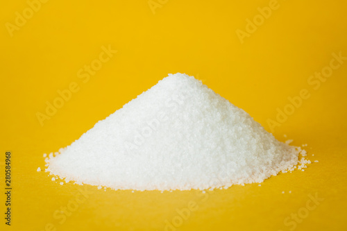 Fotomural  Heap of sugar on yellow background