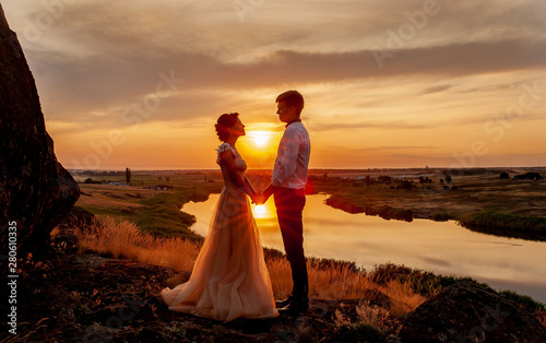 Foto auf Gartenposter Schokobraun Loving couple, boyfriend and girlfriend looking at each other at sunset on the mountain on the background of the river
