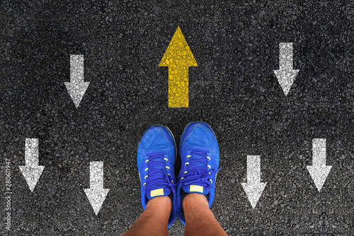 Photo  man shoes on asphalt and opposing direction arrows on asphalt ground, personal p
