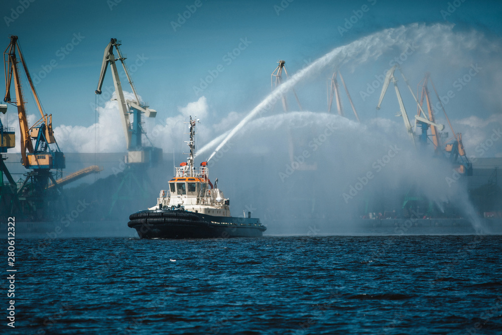 Fototapety, obrazy: A firefighter floating modern tug boat sprays jets of water