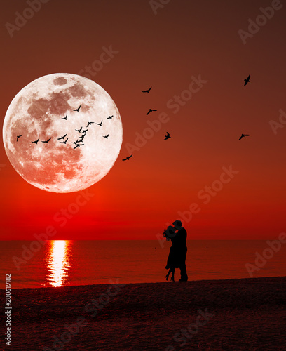 Fotografie, Obraz  Silhouette of a kissing couple under full moon at sunset