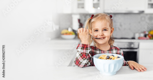 Fotografia Beautiful little girl having breakfast with cereal, milk and banana in kitchen