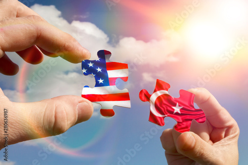 Carta da parati  Two hands assemble a puzzle with the flags of Turkey and America
