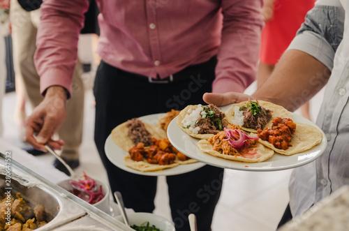 Fotografie, Obraz  Hombres sirviendo comiendo tacos