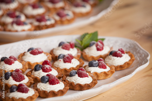 Delicious homemade muffins with vanilla cream cheese and organic blueberries and raspberries on top Canvas Print