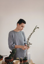 Woman Putting Twig In Vase