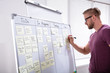 Happy Man Sticking Adhesive Note On White Board