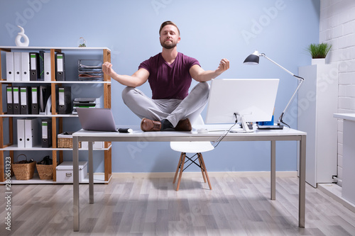 Obraz Businessman Meditating Over Desk - fototapety do salonu