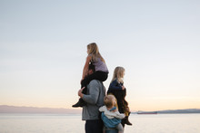 Family Standing On Beach Against Clear Sky