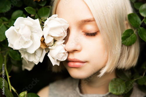 Fotografie, Obraz  Portrait of beautiful young girl with closed eyes in white roses