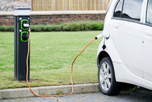 Electric Car Charging With Cable And Vehicle Charge Point At Carpark