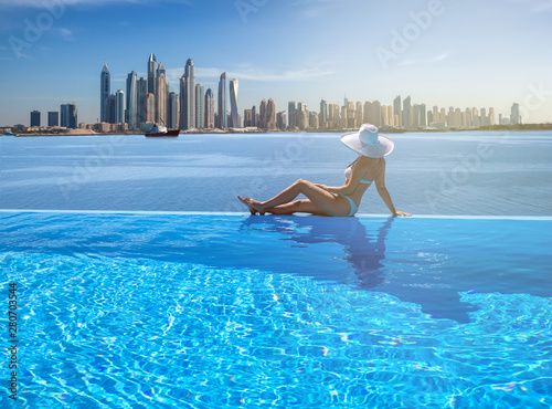 Poster Bleu Beautiful panorama of Dubai Marina skyline in a background with a pool, deck chair and woman with a white hat.