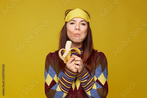 Lovely mixed race young woman holds delicious banana, tastes with pleasure, enjoying likes eating sweets, has good appetite,  wears colorful sweater and sleeping mask on head фототапет