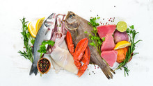 Fresh Fish And Seafood On A White Wooden Background. Flounder, Lobster, Squid, Tuna, Fish. Top View. Free Copy Space.