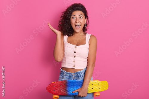 Charming emotional dark haired female looking directly at camera, opening mouth and eyes widely, raising one arm, holding colorful skateboard, wearing pink top and jeans Slika na platnu