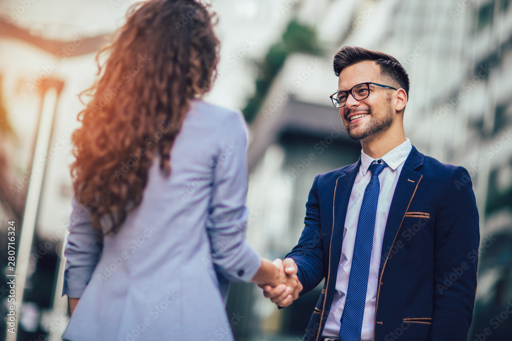 Fototapety, obrazy: Smiling business colleagues greeting each other outdoors