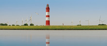 Panorama Von Leuchtturm, Rot Weiß, Windräder Und Jogger, Läufer Auf Einem Deich. Der Himmel Ist Blau, Eine Möwe Fliegt Am Himmel. Ruhige Szene