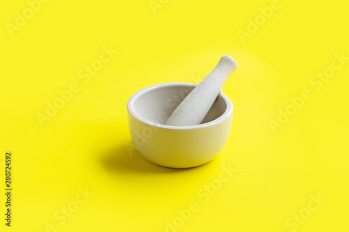 Mortar and pestle on yellow background. Wallpaper Mural