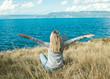 Leinwandbild Motiv Beautiful happy Woman traveler sitting by the sea in mountain su