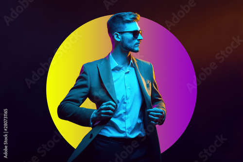 Obraz na plátne Young handsome model posing in a studio in a trendy neon light