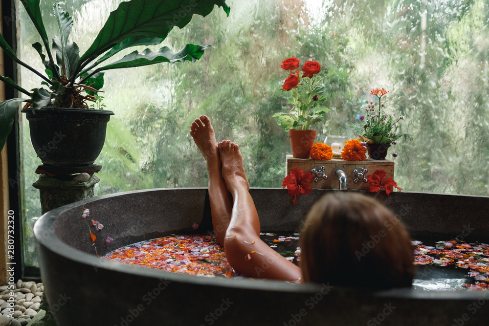 Fototapeta Back view woman relaxing in round outdoor bath with tropical flowers, organic skin care, luxury spa hotel, lifestyle photo. Female legs in bathtub with flower petals