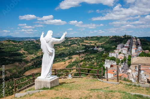 In de dag Zuid-Amerika land The statue of Christ the Redeemer over the town of Pomarico. Basilicata, Italy