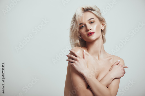 Feeling sexy. Beautiful and slim woman with blond hair covering her breast with her hands and looking at camera while standing against grey background - 280739555